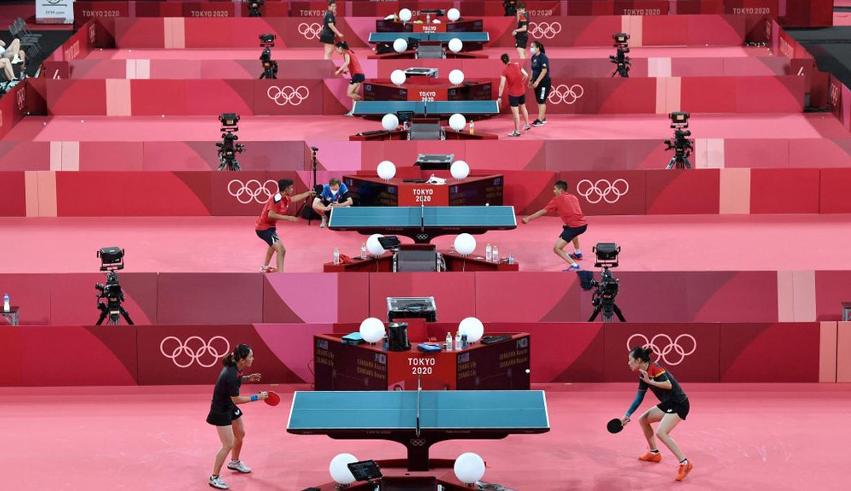 Para pemain tenis meja melakukan sesi latihan jelang Olimpiade Tokyo 2020 di Tokyo Metropolitan Gymnasium, Tokyo, Jepang, Rabu (21/7/2021). Olimpiade Tokyo 2020 akan dibuka pada 23 Juli 2021. (Jung Yeon-je/AFP)