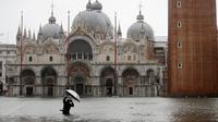 Fotografer mengambil gambar Alun-Alun Santo Markus yang banjir akibat gelombang pasang di Venesia, Italia, Selasa (12/11/2019). Venesia dilanda banjir akibat gelombang pasang setinggi 127 cm. (AP Photo/Luca Bruno)