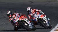 Perjuangan pembalap Ducati, Andrea Dovizioso saat menempel rekan setimnya, Jorge Lorenzo, pada MotoGP Valencia 2017 di Sirkuit Ricardo Tormo. (JOSE JORDAN / AFP)