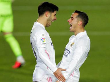 Gelandang Real Madrid, Marco Asensio, melakukan selebrasi bersama Lucas Vazquez usai mencetak gol ke gawang Celta Vigo pada laga Liga Spanyol di Stadion Alfredo Di Stefano, Sabtu (2/1/2021). Real Madrid menang dengan skor 2-0. (AP/Manu Fernandez)