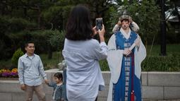 Seorang anak saat difoto selama perayaan Chuseok di sebuah taman di Seoul(5/10). Seperti halnya kebanyakan festival panen lainnya di seluruh dunia, Chuseok dirayakan sekitar ekuinoks musim gugur. (AFP Photo/Ed Jones)