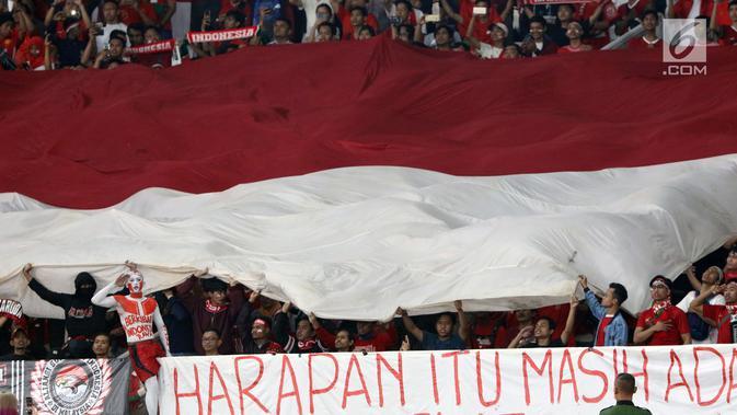 Suporter tim Garuda membentangkan bendera Merah Putih jelang menyaksikan laga Timnas Indonesia melawan Timor Leste pada penyisihan grup B Piala AFF 2018 di Stadion GBK, Jakarta, Selasa (13/11). Indonesia unggul 3-1. (Liputan6.com/Helmi Fithriansyah)