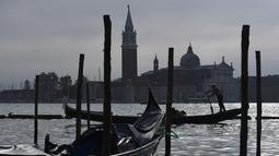 Gondola mengangkut wisatawan yang dekat dengan perairan Riva degli Schiavoni dengan latar gereja San Giorgio Maggiore di Venice (4/11/2019). Di kawasan ini ada pejalan kaki yang ramai meskipun sering penuh sesak di sepanjang tepi pantai, yang terletak di Cekungan St. Mark. (AFP Photo/Miguel Medina)