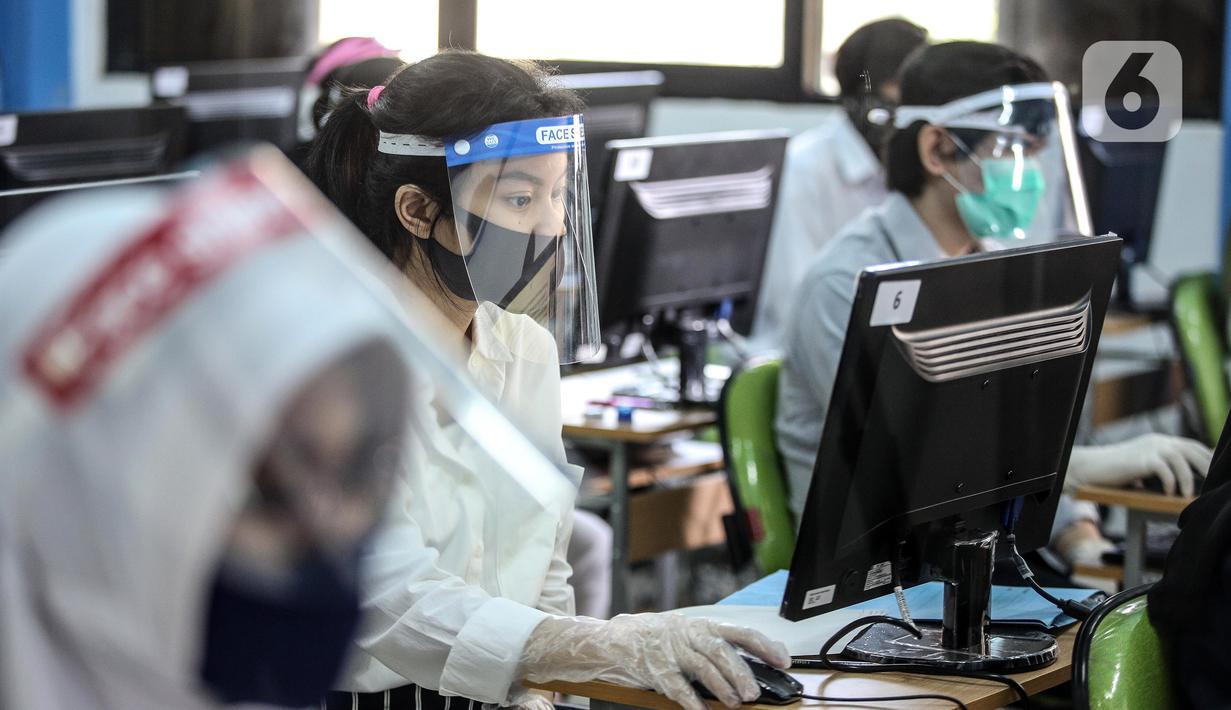 Peserta mengenakan masker, pelindung wajah, dan sarung tangan saat mengikuti Seleksi Bersama Masuk Perguruan Tinggi Negeri (SBMPTN) di Universitan Negeri Jakarta, Minggu (5/7/2020). Sebanyak 42.463 peserta mengikuti SBMPTN dengan prosedur protokol kesehatan. (Liputan6.com/Faizal Fanani)