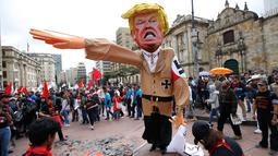 Patung karakter Presiden AS Donald Trump disiapkan sebelum dibakar saat aksi protes pada peringatan Hari Buruh di Bogota, Kolombia (1/5). Ribuan orang di Kolombia turun ke jalan untuk memperingati Hari Buruh. (AP/Fernando Vergara)