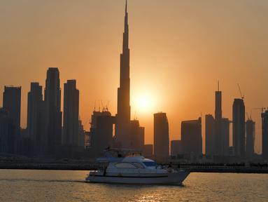 Matahari terbenam di belakang bangunan tertinggi di dunia Burj Khalifa dan gedung-gedung bertingkat lainnya, di Dubai, Uni Emirat Arab pada Sabtu (12/9/2020). (Photo by Karim SAHIB / AFP)