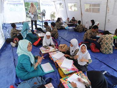 Murid SMP dan SMA Sekolah Khusus Assalam 01 melaksanakan ujian di tenda darurat halaman SKh Assalam 02, Ciater, Serpong, Tangerang Selatan, Selasa (3/12/2019). Sebanyak 84 murid penyandang tunarungu, tunawicara, dan tunagrahita terpaksa mengikuti ujian di tenda darutat. (merdeka.com/Arie Basuki)