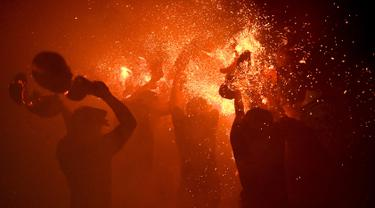 Sejumlah pemuda berpartisipasi dalam upacara perang api, yang secara lokal dikenal sebagai Siat Geni, di sebuah kuil di Tuban dekat Denpasar, Bali (13/10/2019). Ritual Siat Geni diadakan setiap tahun untuk mendorong kaum muda berani dan menolak nasib buruk. (AFP Photo/Sonny Tumbelaka)