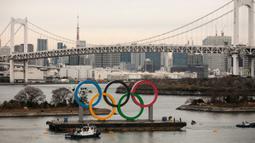 Kapal tongkang membawa Cincin Olimpiade dekat Rainbow Bridge di Distrik Odaiba, Tokyo, Jepang, Jumat (17/1/2020). Cincin Olimpiade dengan tinggi 15,3 meter dan panjang 32,6 meter tersebut akan berada di sana hingga Olimpiade 2020 berakhir. (AP Photo/Jae C. Hong)