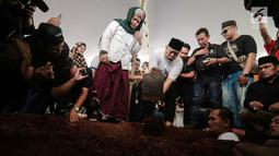Komedian Indro Warkop menggali makam untuk mendiang istrinya, Nita Octobijanthy di TPU Tanah Kusir, Jakarta, Rabu (10/10). Nita meninggal di usia 59 tahun. (Liputan6.com/Faizal Fanani)