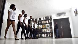 Wanita dan pria muda ikut serta dalam pelatihan catwalk di agen model Fatim Sidime di Abidjan, Pantai Gading (20/12). Mereka mengikuti pelatihan karena industri fashion dan model di Afrika terus mengalami perkembangan. (AFP Photo/Sia Kambou)