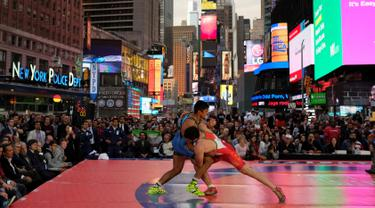 Pegulat dari AS, Zahid Valencia (biru) saat melawan Mojtaba Goleij dari Iran pada kejuaraan gulat Beat the Streets, Times Square, New York (19/5). Pertandingan gulat ini sontak dipadati penonton karena digelar ditengah kota terbuka. (REUTERS/Adrees Latif)