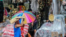 Seorang pria menggunakan kardus sebagai payung saat berjalan melewati banjir di tengah hujan deras yang tiba-tiba mengguyur di sebuah pasar dekorasi Natal di Manila, Filipina (9/12/2020). (Xinhua/Rouelle Umali)