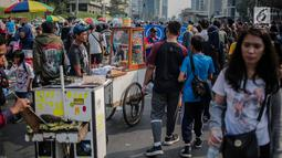 Warga melewati pedagang kaki lima (PKL) yang berjualan di kawasan car free day (CFD), Bundaran HI, Jakarta, Minggu (4/8/2019). Kurangnya pengawasan petugas menyebabkan banyak PKL berjualan tidak pada tempat yang telah disediakan oleh Pemprov DKI Jakarta. (Liputan6.com/Faizal Fanani)