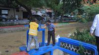 Wali Kota Tangerang Arief R Wismansyah sibuk membuka pintu air yang ada di tiap anak Sungai Cisadane. (Liputan6.com/Pramita Tristiawati)