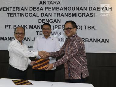 Mendes PDTT Eko Putro Sandjojo (tengah) menyaksikan Sekjen Kemendes PDTT Anwar Sanusi (kiri) dan Dirut Bank Mandiri Kartika Wirjoatmodjo (kanan) bertukar naskah MoU kerja sama di Kantor Kemendes PDTT, Jakarta, Senin (30/9/2019). (Liputan6.com/Angga Yuniar)