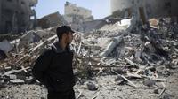 Polisi Palestina berdiri dekat reruntuhan bangunan kantor The Associated Press yang hancur akibat serangan udara Israel di Kota Gaza, Sabtu, 15 Mei 2021. Gedung tersebut juga menampung Al Jazeera dan sejumlah kantor serta apartemen. (AP Photo/Khalil Hamra)