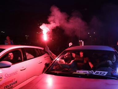 Suporter menyalakan flare saat menyaksikan pertandingan Viktoria Plzen dan Sparta Praha di sebuah bioskop drive-in di Pilsen, Republik Ceko, Rabu (27/5/2020). Di tengah pandemi COVID-19, suporter Ceko dapat menyaksikan pertandingan bola lewat layar di bioskop drive-in. (AP Photo/Petr David Josek)