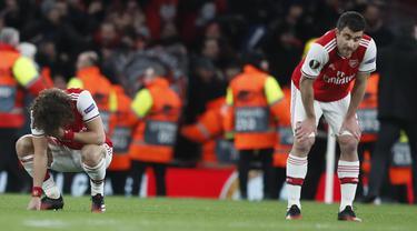 Pemain Arsenal tertenduk lesu usai pertandingan melawan Olympiakos pada leg kedua babak 32 besar Liga Europa di stadion Emirates, London, Kamis (27/2/2020).  Olympiakos menang 2-1 dan lolos dengan unggul agregat gol tandang 2-2. (AP Photo/Frank Augstein)