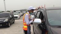Petugas Tol Cipali saat melayani pembayaran tol di Gerbang Tol Palimanan. (Liputan6.com/Panji Prayitno)