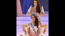 Miss World 2013, Megan Young saat memakaikan mahkota berwarna biru di atas kepala Rolene Strauss di London, Minggu (14/12/2014). (AFP PHOTO/Leon Neal)