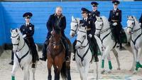 Vladimir Putin mengendarai kuda di dalam fasilitas pelatihan di Moskow, Rusia, dengan diapit oleh para polisi wanita dari Resimen Polisi Operasional Pertama (1st Operational Police Regiment) pada hari Kamis, 7 Maret 2019. (Mikhail Metzel/TASS)