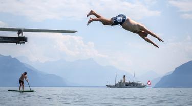 Seorang pria melompat ke Danau Jenewa di Saint Saphorin, Swiss barat saat gelombang panas melanda seluruh Eropa utara (31/7). Akibat gelombang panas suhu di beberapa bagian Swiss mencapai 35 Derajat. (AFP Photo/Fabrice Coffrini)