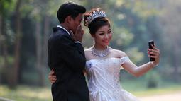 Sepasang pengantin baru berswafoto saat disela pengambilan foto pernikahan mereka di kompleks kuil Angkor Wat, sebuah candi ikonik dan bersejarah di Kamboja, 14 Maret 2018. Candi ini masuk dalam daftar Situs Warisan Dunia UNESCO. (AP Photo/Heng Sinith)