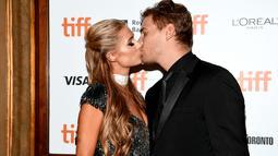 """Paris Hilton dan kekasihnya Chris Zylka berciuman saat menghadiri pemutaran perdana """"The Death And Life Of John F. Donovan"""" selama Festival Film Internasional Toronto 2018 di Winter Garden Theatre Toronto, Kanada (10/9). (Emma McIntyre/Getty Images/AFP)"""