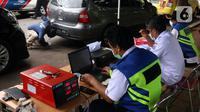 Petugas memeriksa emisi kendaraan di Jakarta Barat, Rabu (13/1/2021). Dinas Lingkungan Hidup DKI Jakarta mengumumkan kendaraan yang tidak mengikuti uji emisi atau tidak lulus uji emisi gas buang akan dikenakan disinsentif tarif parkir yang tinggi dan tilang. (Liputan6.com/Angga Yuniar)