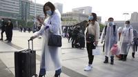 Penumpang yang mengenakan masker dan mantel hujan untuk berkumpul di luar Stasiun Hankou, Wuhan, Provinsi Hubei, China, Rabu (8/4/2020). Setelah 11 minggu lockdown, layanan kereta di kota yang menjadi titik awal pandemi virus corona COVID-19 ini kembali beroperasi. (AP Photo/Ng Han Guan)