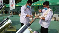 Dua koki memasukkan daging sate ke dalam tabung logam dan dimasak menggunakan kompor tenaga surya di Dezhou, Shandong Timur, Cina, 2 Agustus 2018. Koki memasak pada festival masak menggunakan kompor tenaga surya di Cina. (AP Foto/Fu Ting)