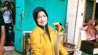 Iin Ayu (55) bersama satu di antara ular King Kobra peliharaannya di rumahnya di Kelurahan Karangpucung, Kecamatan Purwokerto Selatan, Kabupaten Banyumas, Selasa (17/12/2019). (Liputan6.com/Rudal Afghany Dirgantara)