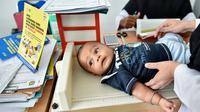Petugas memeriksa bayi sebelum menyuntikan Vaksin Campak dan Rubella (MR) saat dilakukan imunisasi di sebuah puskesmas, Banda Aceh, Rabu (19/9). Pemprov Aceh akhirnya membolehkan pelaksanaan vaksinasi MR yang mengandung enzim babi (CHAIDEER MAHYUDDIN/AFP)