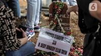 Bunga ditempatkan pada nisan mantan artis cilik Cecep Reza saat pemakaman di TPU Layur Penggilingan, Jakarta, Rabu (20/11/2019). Cecep Reza meninggal pada usia 31 tahun karena penyakit jantung. (Liputan6.com/Faizal Fanani)