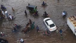 Sejumlah warga melintasi banjir saat beraktivitas setelah hujan deras di Lahore, Pakistan (16/7/2019). Di Kashmir yang dikelola Pakistan, para pejabat pemerintah mengatakan sedikitnya 23 orang tewas setelah hujan lebat memicu banjir bandang. (AFP Photo/Arif Ali)