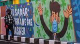 Seorang perempuan melewati mural yang mengajak orang untuk memakai masker di tengah pandemi Covid-19 di Surabaya, Minggu (25/10/2020). Mural di sepanjang dinding itu sebagai sarana imbauan kepada masyarakat untuk menerapkan protokol kesehatan pencegahan penularan COVID-19. (Juni Kriswanto/AFP)