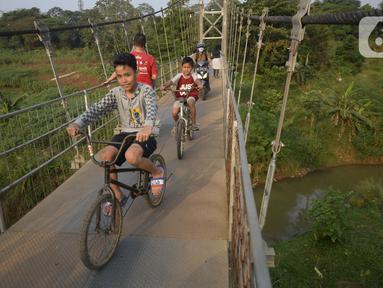 Anak-anak bersepeda melintasi jembatan gantung di Kelurahan Curug, Bojongsari, Kota Depok, Jawa Barat, Senin (24/8/2020). Setiap sore, warga sekitar bermain di jembatan tersebut sambil menikmati matahari tenggelam. (merdeka.com/Dwi Narwoko)