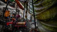 Pekerja mengoperasikan mesin saat melakukan pengeboran di sumur minyak ilegal di Minhla, Myanmar, 10 Maret 2019. Para pekerja dapat mengebor hingga satu kilometer ke dalam tanah. (Ye Aung THU/AFP)