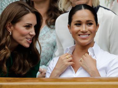 Duchess of Cambridge Kate Middleton (kiri) dan Duchess of Sussex Meghan Markle berbincang saat menyaksikan pertandingan final tunggal putri Wimbledon 2019 antara Serena Williams dengan Simona Halep di All England Lawn Tennis and Croquet Club, London, Inggris, Sabtu (13/7/2019). (BEN CURTIS/POOL/AFP)