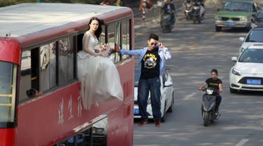 Pesulap Lei Xin (kanan) berada di luar bus tingkat sambil melayang dengan seorang wanita bergaun pengantin di Zhengzhou, Provinsi Henan, China, (15/10/2015). Aksi bertujuan mengajak masyarakat untuk tidak takut menikah diusia muda. (REUTERS/Stringer)