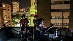 Aktivis @lanuevabandadelaterraza memproyeksikan gambar di dinding gedung di Medellin, Kolombia, 9 Agustus 2020. Karena protes dibungkam akibat lockdown COVID-19, tuntutan sosial dan politik diproyeksikan ke gedung-gedung di Amerika Latin yang dibagikan melalui jejaring sosial (JOAQUIN SARMIENTO/AFP)