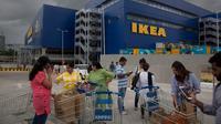 Sejumlah pembeli berdiri di luar IKEA saat membuka toko pertamanya di Hyderabad, India, Kamis (9/8). Lebih dari 200 pembeli membentuk antrean dan menunjukkan antusiasme mereka dengan dibukanya furnitur asal Swedia untuk pertama kali. (AP/Mahesh Kumar A.)