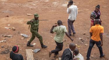 Aparat kepolisian memukuli pria saat membubarkan orang-orang yang masih berkeliaran di Kampala, Uganda (26/3/2020). Presiden Uganda Yoweri Museveni mengimbau masyarakatnya untuk tinggal di rumah selama 32 hari setelah 14 kasus positif Covid-19 teridentifikasi di negara tersebut. (AFP/Badru Katumba)