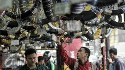 Pelanggan jasa servis motor tengah melihat aksesoris kendaraan di bengkel di kawasan Pasar Minggu, Jakarta, Kamis (30/6). Jelang Lebaran, bengkel motor ramai dikunjungi pemudik motor. (Liputan6.com/Yoppy Renato)