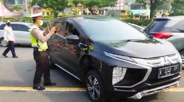 Polisi menempel stiker khusus untuk kendaraan plat Surabaya dan Gresik saat larangan mudik. (Dian Kurniawan/Liputan6.com)