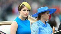Putri Inggris Eugenie (kiri) dan Putri Beatrice mengenakan topi atau fascinator unik saat menghadiri ajang pacuan kuda Royal Ascot di Ascot, Inggris, Selasa (18/6/2019). Royal Ascot menjadi ajang bagi wanita Inggris untuk tampil dengan fascinator unik. (Mike Egerton/PA via AP)