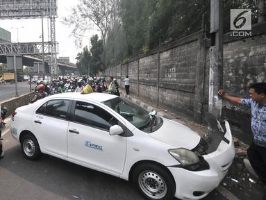 Pengendara sepeda motor tersendat saat melintasi lokasi kecelakaan taksi menabrak tiang di Jalan Ahmad Yani, Jakarta, Rabu (1/8). Kecelakaan terjadi setelah sopir taksi berusaha menghindari pengendara sepeda motor di depannya. (Merdeka.com/Iqbal Nugroho)