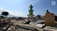 Warga membawa papan bertuliskan Kami Butuh Bantuan Pak Jokowi di atas reruntuhan puing pasca gempa bumi dan tsunami di Jalan Trans Sulawesi, Palu, Sulawesi Tengah, Kamis (4/10). (Liputan6.com/Fery Pradolo)