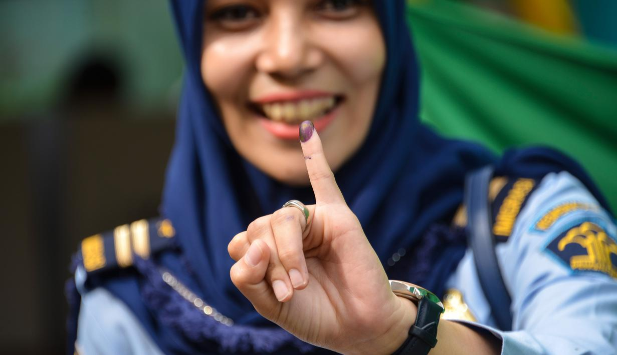 Warga menunjukkan jari kelingking usai mencoblos pada pemungutan suara ulang pemilu 2019 di TPS-6 Desa Lamteumen Timur, Banda Aceh, Aceh, Kamis (25/4). Pemungutan suara ulang karena adanya penggunaan formulir C6 pemilih yang telah meninggal pada pemilu 17 April lalu. (CHAIDEER MAHYUDDIN/AFP)
